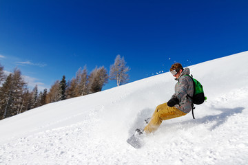 Snowboarder in action on a sunny day in the Italian Alps