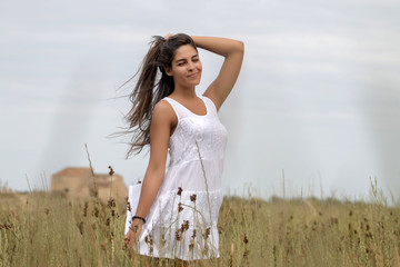 Close view of a beautiful woman on a white dress on the countryside.
