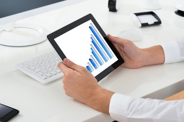 Businessperson Analyzing Graph On Digital Tablet