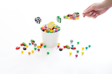 female hand holding a scoop of candy with a overflowing bucket of candy