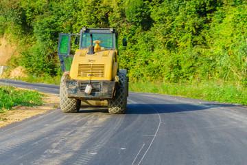 Yellow bulldozer on the road