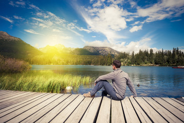 Man sitting near alpine mountain lake