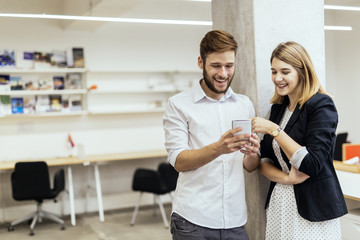 Two colleagues smiling while looking at the phone in an office