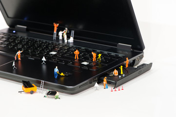 Team of Miniature workers repairing Laptop.