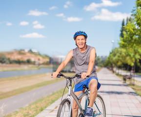 Cheerful senior posing with his bike on a sidewalk