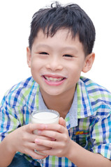 Asian boy drinking a glass of milk over white background