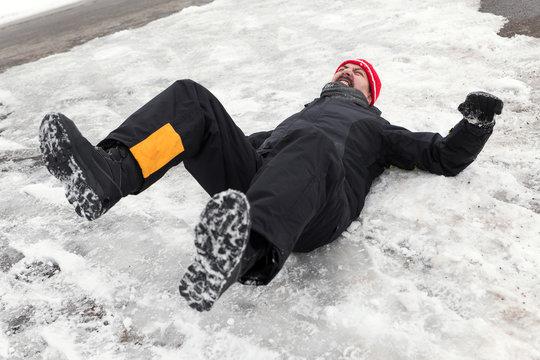 Mann liegt auf Straße mit Glatteis