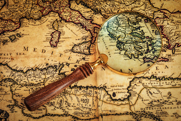 Old vintage magnifying glass on ancient map