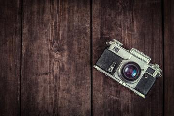 Old retro vintage camera on grunge wooden background
