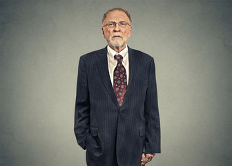 Portrait of a serious senior businessman on gray wall background