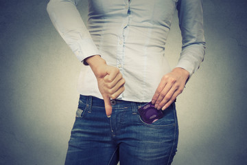woman with condom in her pocket giving thumbs down