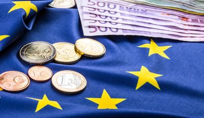 Euro coins. Euro currency. Euro money. European flag and euro money.  Coins and banknotes European currency freely laid on the European flag