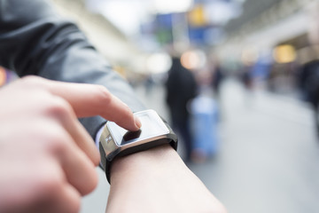 In hall station a man using his smartwatch. Close-up hands