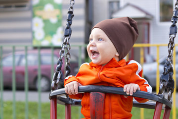 Joyful toddler on a swing