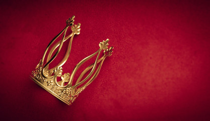 Royal golden crown on red velvet