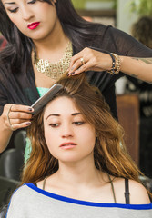 Brunette facing camera getting hair done by professional stylist