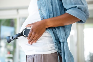 Pregnant woman placing headphones on her stomach