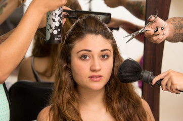 Brunette model facing camera is getting makeup and hair done by