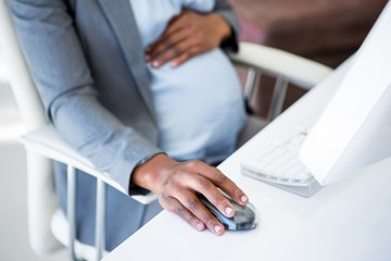 Smiling pregnant businesswoman at work