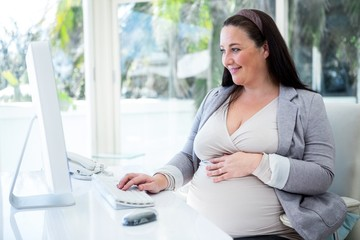Pregnant businesswoman working on her computer