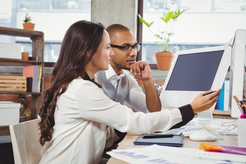 Woman showing computer to colleague