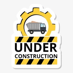 Truck with sand under construction sign