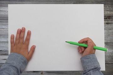 child holding pen on blank sheet of paper. kid draws on white paper.
