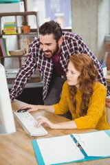 Woman and man looking at computer in office