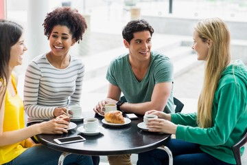 Happy students having coffee together