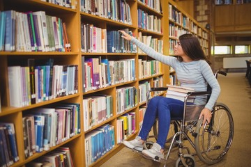 Disabled female student selecting book