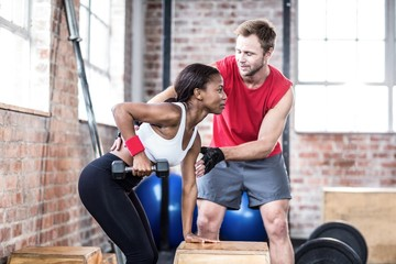 Muscular woman lifting dumbbell with her trainer