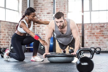 Trainer helping muscular man exercise
