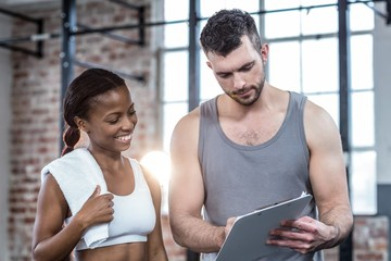 Woman discussing her performance on clipboard with a trainer