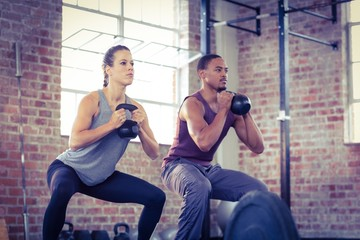 Fit couple lifting kettle bells