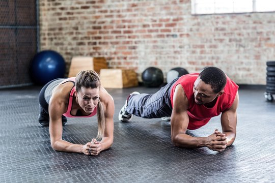 Fit couple doing plank exercises together