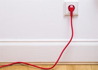 Das Foto zeigt ein rotes Stromkabel in einer Steckdose