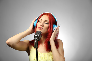 Beautiful young woman with microphone and headphones on gray background
