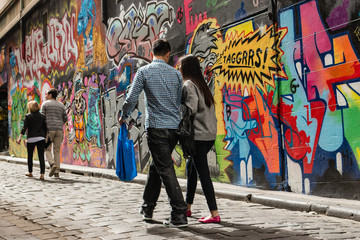 people walking past graffiti wall in Melbourne