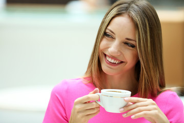 Beautiful young woman drink coffee in cafe