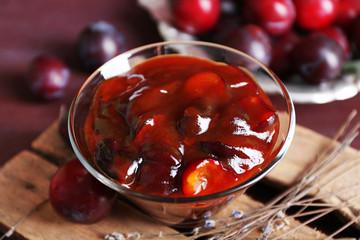 Tasty homemade plum jam in glass saucer on wooden board, closeup