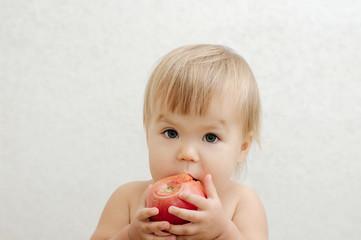 child bitting tomato