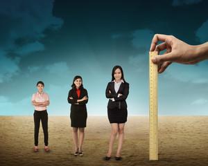 Hand holding wooden ruler, mesuring employee performance