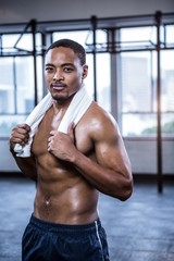 Fit shirtless man with towel on shoulders