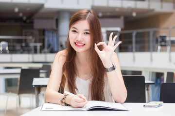 Portrait of thai adult beautiful girl write a book and smile in university.