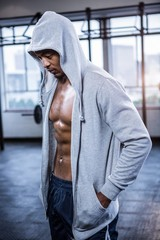 Fit shirtless man with hooded jumper
