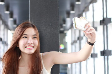 Portrait of thai adult beautiful girl using her smart phone Selfie.