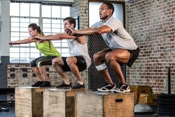 Fit people doing squat jumps