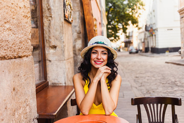 beautiful young brunette woman in a yellow dress and hat on the streets of the old town