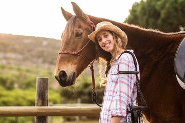 Smiling woman standing with her horse