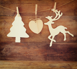 image of wooden decorative christmas tree and reindeer hanging on a rope over wooden background
